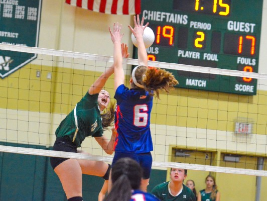Nashoba junior middle hitter Brynne McConnell spikes the ball past the outstretched arms of North MiddlesexÕs Maddy Harrington during Saturday morningÕs match in Bolton.  SENTINEL & ENTERPRISE / ED NISER
