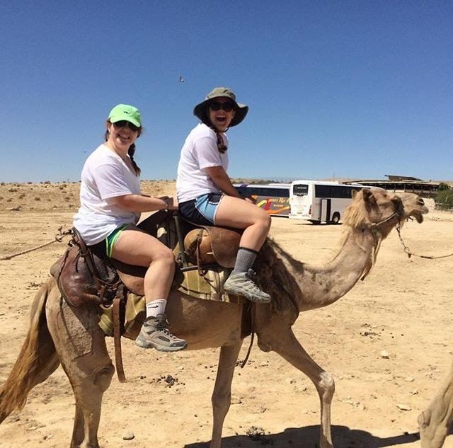 Hannah Honig and Julia Cohen riding a camel in the Negev Desert.