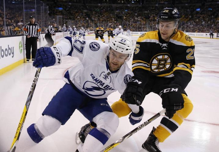 Tampa Bay Lightnings Jonathan Drouin (27) and Boston Bruins Brandon Carlo (25) battle along the boards during the first period of an NHL hockey game in Boston, Sunday, Nov. 27, 2016. (AP Photo/Michael Dwyer)
