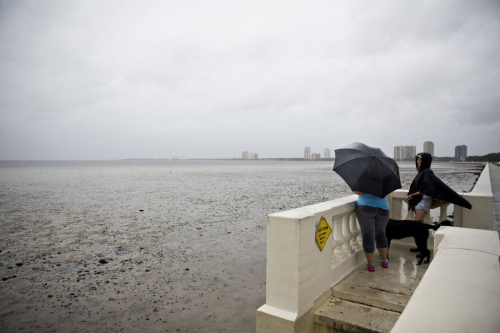 Residents look over Tampa Bay, where the normally 3' deep water had receded approximately 150 ft. off shore, ahead of Hurricane Irma in Tampa, Florida, U.S., on Sunday, Sept. 10, 2017. Hurricane Irma smashed into Southern Florida as a Category 4 storm, driving a wall of water and violent winds ashore and marking the first time since 1964 the U.S. was hit by back-to-back major hurricanes. Photographer: Daniel Acker/Bloomberg via Getty Images